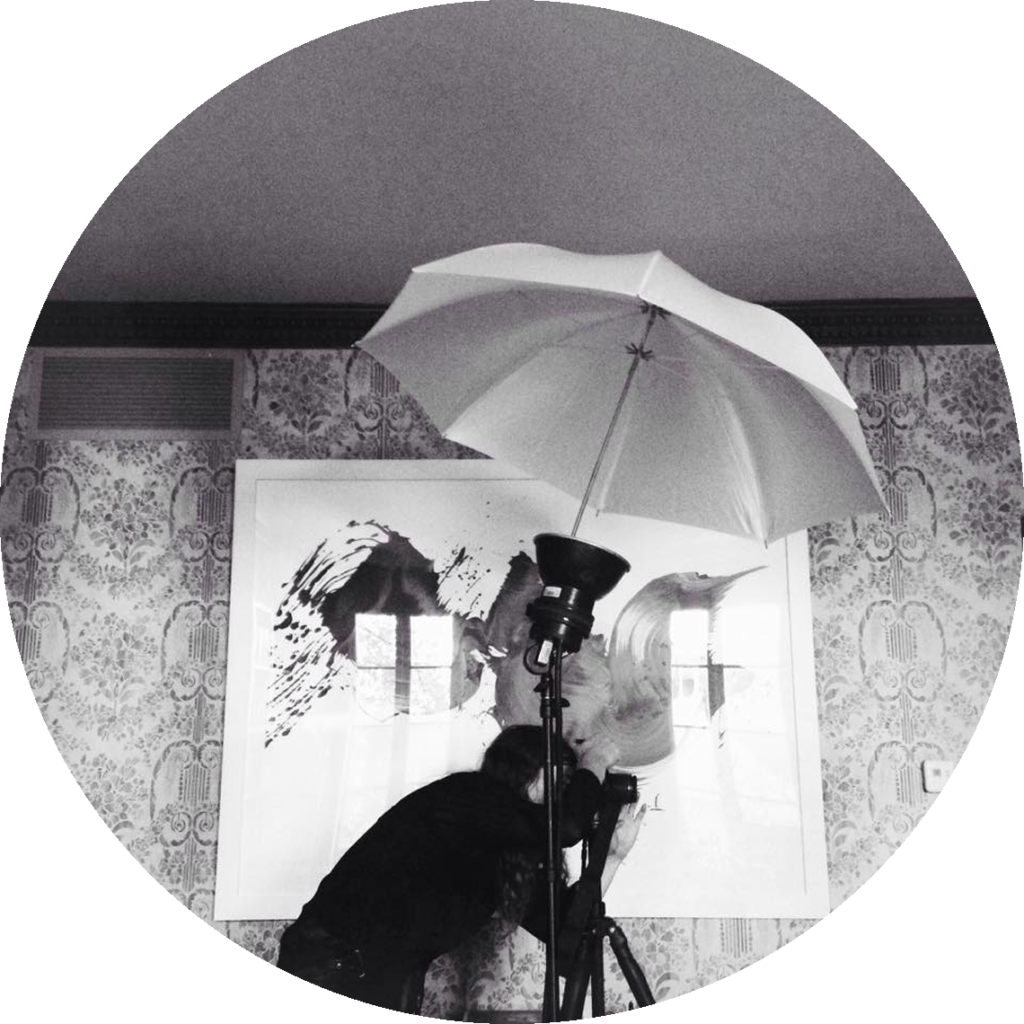 Image of a woman looking through the lens of a camera with an umbrella overhead
