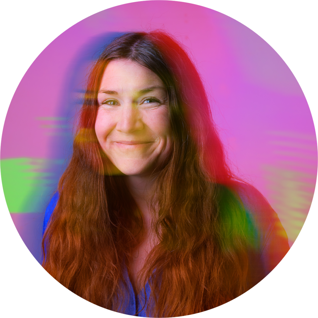 Smiling woman, Lauren, with long medium brown coloured hair on a pink background with green lens flare